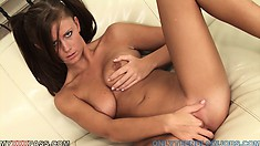 The cutie lies on the couch with her legs wide open playing with her shaved pussy