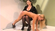 Adorable blonde with perky tits bends over and a busty brunette spanks her ass hard
